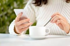 Kvinna som har en kopp kaffe på ett kafé och använder en telefon royaltyfria foton