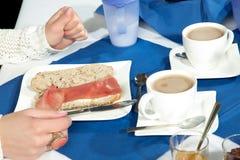 Kvinna som har en skinkarulle för frukost royaltyfri bild