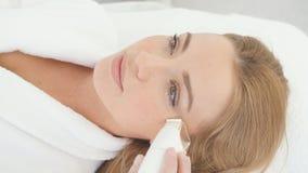 Kvinna som har en stimulerande ansikts- behandling från en terapeut stock video