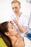 Kvinna som har en stimulerande ansikts- behandling från en terapeut Royaltyfri Fotografi