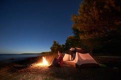 Kvinna som har en vila på natten som campar nära det turist- tältet, lägereld på havskust under stjärnklar himmel fotografering för bildbyråer