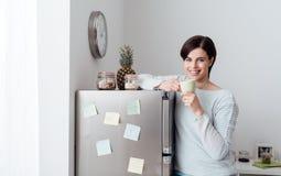 Kvinna som har ett kaffeavbrott hemma royaltyfri bild