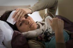 Kvinna som har feber som rymmer hennes panna Royaltyfria Bilder
