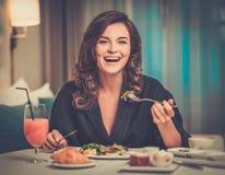 Kvinna som har frukosten i ett hotell royaltyfria foton