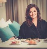 Kvinna som har frukosten i ett hotell arkivfoto