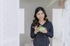 Kvinna som har frukosten på fönster arkivbild