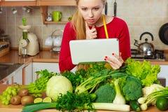 Kvinna som har gröna grönsaker som tänker om matlagning royaltyfri bild
