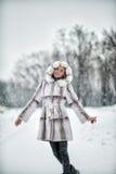 Kvinna som har gyckel på den insnöade vinterskogen Arkivbild