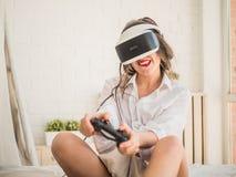 Kvinna som har gyckel som tycker om VR och spelar lekar Arkivbilder