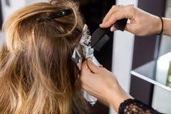 Kvinna som har hår att färgas av kosmetologen At Parlor Fotografering för Bildbyråer