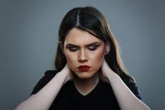Kvinna som har huvudvärk eller den smärtsamma halsen Royaltyfri Bild