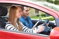 Kvinna som har körningskurs med instruktören royaltyfri foto