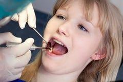Kvinna som har kindtänder att undersökas av en tandläkare. arkivfoto