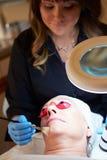Kvinna som har kosmetisk behandling för Dermo slitning på Spa Royaltyfria Bilder