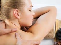 Kvinna som har kroppmassage i brunnsortsalongen arkivbild