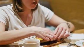 Kvinna som har lunch i en restaurang med Caucasian kokkonst N?rbild Kvinnan ?ter den varma saftiga khachapurien som doppar ett st lager videofilmer