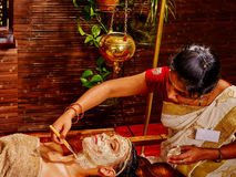 Kvinna som har maskeringen på ayurvedabrunnsorten royaltyfri bild