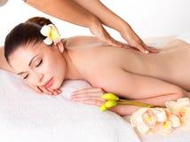 Kvinna som har massage av kroppen i brunnsortsalong arkivfoto