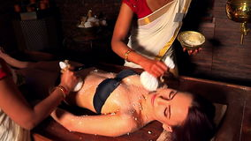 Kvinna som har massage med påsen av ris i brunnsortsalong arkivfilmer