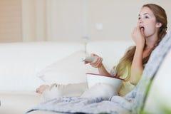 Kvinna som har popcorn, medan tycka om en film Royaltyfri Fotografi