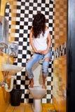 Kvinna som har problem med toalettplatsen Arkivbild