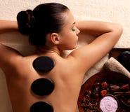 Kvinna som har stenmassage i brunnsortsalong Royaltyfri Fotografi