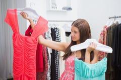 Kvinna som har svårigheter som väljer klänningen Royaltyfria Bilder