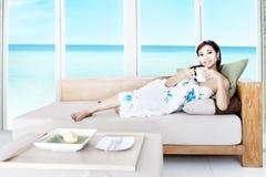Kvinna som har tea i strandlägenhet Royaltyfri Fotografi