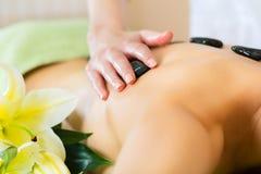 Kvinna som har varm stenmassage för wellness Royaltyfri Bild