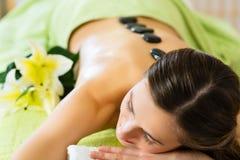 Kvinna som har varm stenmassage för wellness Arkivfoto