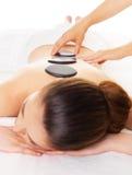 Kvinna som har varm stenmassage i brunnsortsalong. Fotografering för Bildbyråer