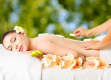 Kvinna som har varm stenmassage i brunnsortsalong. Royaltyfria Bilder