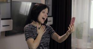 Kvinna som har video pratstund genom att anv?nda smartphonen som tycker om att prata till v?nnen fotografering för bildbyråer