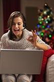 Kvinna som har video pratstund med familjen som är främst av julträd Arkivbild