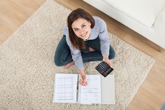 Kvinna som hem beräknar finanser på filten Arkivfoton