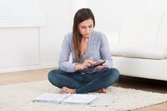 Kvinna som hem beräknar finanser på filten Arkivbilder