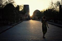 Kvinna som hem går i solnedgången i den historiska walled staden av den siden- vägen arkivbild