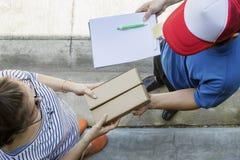 Kvinna som hemifrån accepterar på linjen man för leverans för shoppingprodukt royaltyfri bild