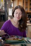 Kvinna som hemma äter frukosten Arkivfoto