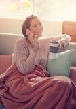 Kvinna som hemma använder en mobiltelefon fotografering för bildbyråer
