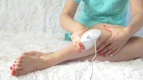 Kvinna som hemma använder en photoepilator för ett hårborttagningstillvägagångssätt arkivfilmer