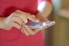 Kvinna som hemma använder hennes mobila smarta telefon Arkivfoton