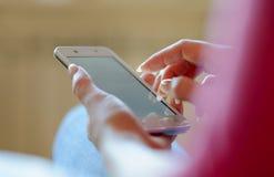 Kvinna som hemma använder hennes mobila smarta telefon Royaltyfria Bilder