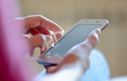 Kvinna som hemma använder hennes mobila smarta telefon Arkivbilder
