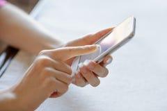 Kvinna som hemma använder hennes mobila smarta telefon Royaltyfri Bild