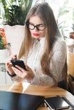 Kvinna som hemma använder mobiltelefonen och bärbara datorn Royaltyfria Bilder