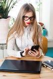 Kvinna som hemma använder mobiltelefonen och bärbara datorn Arkivbilder