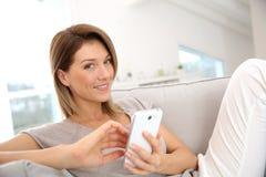 Kvinna som hemma använder smartphonen Royaltyfri Foto