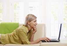 Kvinna som hemma använder datoren Fotografering för Bildbyråer