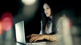 Kvinna som hemma arbetar på bärbara datorn på natten lager videofilmer
